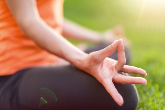 Hand detail of a girl meditation and taking a yoga pose at sunset under trees